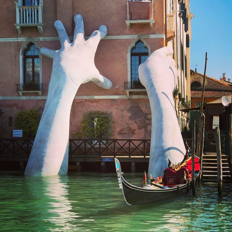 Giant hands rise from a canal in Venice to send a powerful message about climate change
