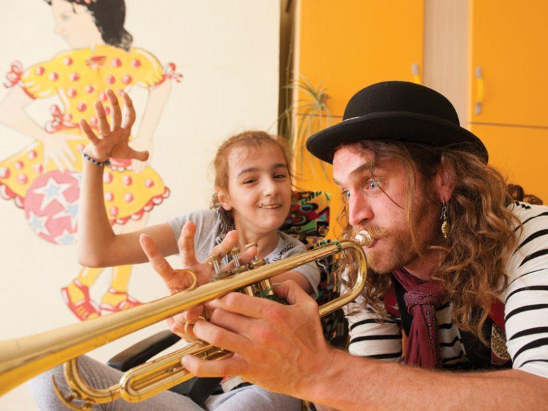 Ένας «στρατός χαράς» από κλόουν, μάγους και καλλιτέχνες, ταξιδεύει σε καταυλισμούς και κάνει να χαμογελούν τα παιδιά που το έχουν ανάγκη